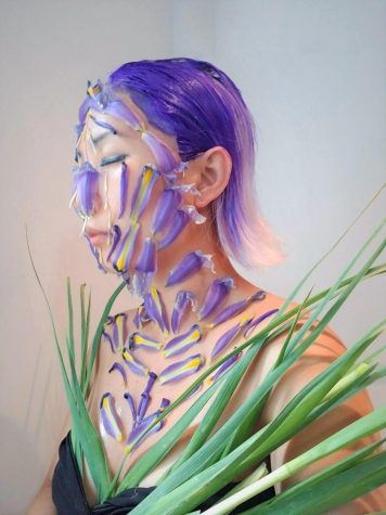Blond Jenny covered in purple iris flower petals and leaves that match her short lavender hair